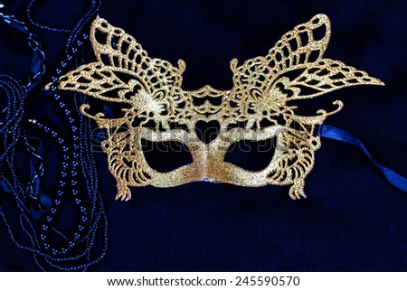 golden carnival mask on dark background - stock photo