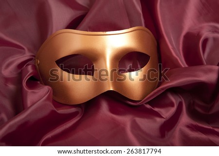Golden carnival mask on red satin background  - stock photo