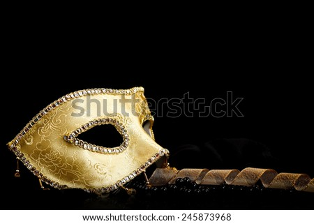 Golden carnival mask with ribbon and pearls, black background - stock photo