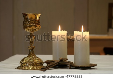Golden chalice and two burning candles - stock photo