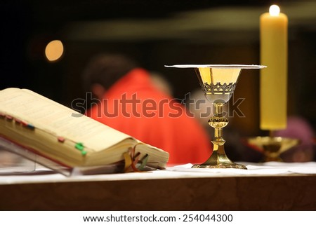 Golden chalice on the altar during the distribution of Holy Communion - stock photo