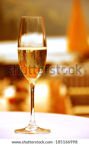 Golden champagne glass outdoor at sunset - stock photo