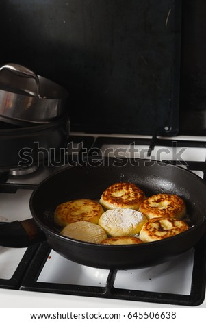 Golden cheese pancakes fried in a pan. Syrniki. Cottage cheese pancake. Curd fritters