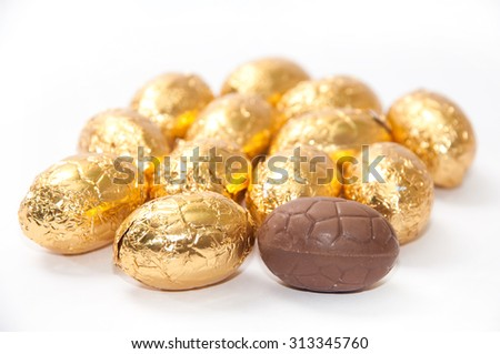 Golden chocolate easter egg on the white background. - stock photo