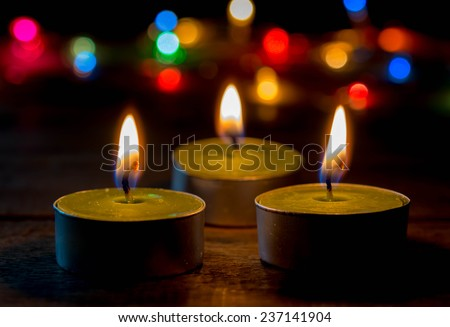 Golden Christmas background - burning advent candle on old wood with blurring lights  - stock photo