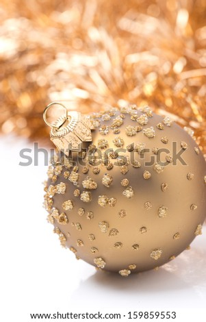golden Christmas ball and tinsel, close-up, isolated on white