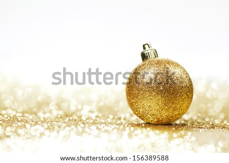 Golden christmas ball on glitter background with white copy space - stock photo