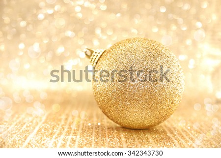 Golden Christmas ball on shiny background with copy space for text. Selective focus. - stock photo