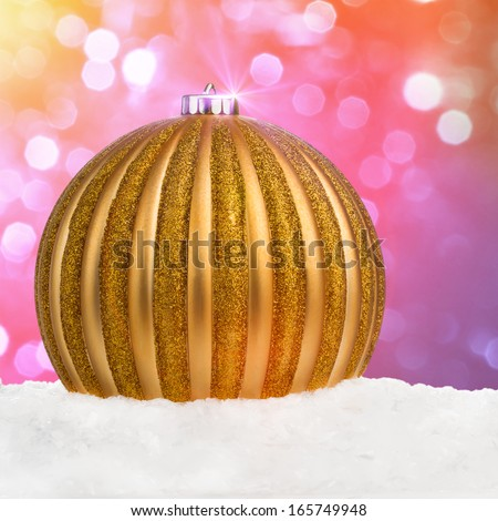 Golden Christmas ball on snow over festive defocused background with copy-space - stock photo