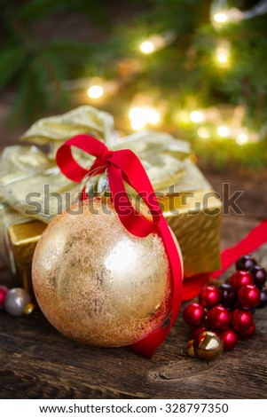 golden  christmas ball with bow and gift box with defocused christmas lights in background - stock photo