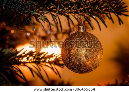 Golden Christmas ball with glittering lights hanging on the tree - stock photo