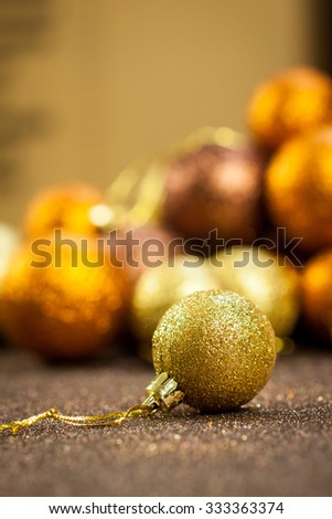 Golden Christmas bauble background with selective focus to a single glitter ball in the foreground with a blurred pile behind giving a warm ambiance and copyspace for your seasonal greeting - stock photo