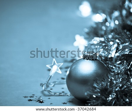 Golden Christmas bauble with star-shaped lights and tinsel, very shallow DOF - stock photo