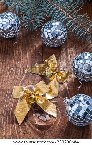 golden christmas bows and mirror disco balls with pinetree branch on old wooden board - stock photo