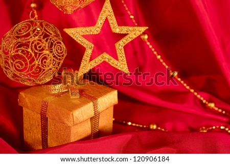 Golden christmas decoration and gift on red fabric background