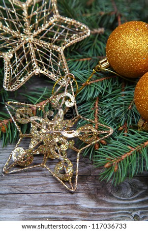 Golden Christmas decorations and spruce branches on a wooden table