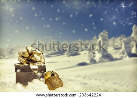 Golden Christmas decorations in the snow, snow cowered pine trees in the background - stock photo