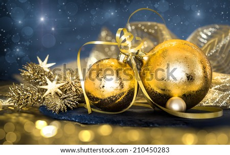Golden Christmas decorations on dark abstract background. Shallow DOF; focus on the ribbon knot