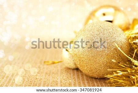 Golden Christmas decorations on shiny background with copy space for text. Christmas background or greeting card. Selective focus - stock photo