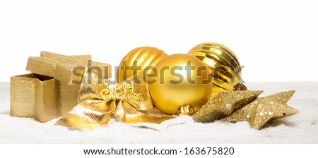 golden christmas decorations over snow