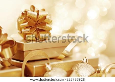 Golden christmas gift box and christmas balls on bokeh light background - stock photo