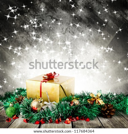 Golden christmas gift box with christmas balls on wood planks over dark background with light - stock photo