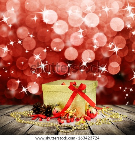 Golden christmas gift box with christmas balls on wooden planks over red blured background