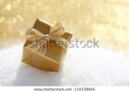 Golden christmas gift on white snow background