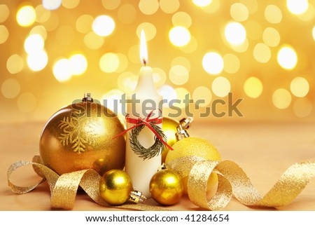 Golden Christmas ornament and candle with blur light on background.