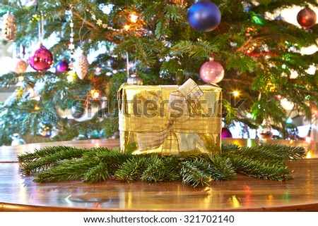 Golden christmas present, Christmas tree - stock photo
