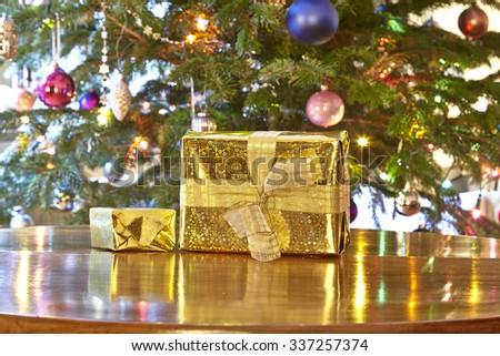 Golden christmas presents, Christmas tree - stock photo