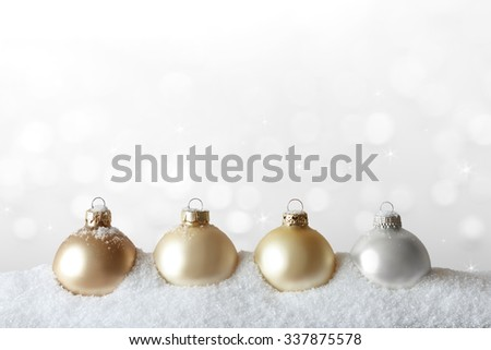Golden christmas tree ornaments on snow in front of sparkling white background, copy or text space - stock photo
