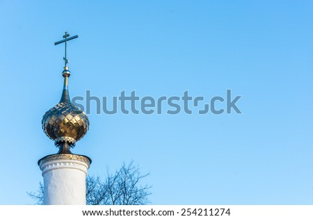 Golden Church steeple with a cross on the background of blue sky. - stock photo