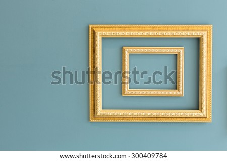 Golden classic picture frames isolated on greenish yellow wall. - stock photo