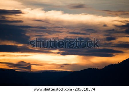 golden cloud and sky during sunset with silhouette of mountain