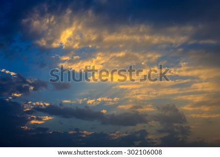 Golden clouds on sunset in evening sky - stock photo
