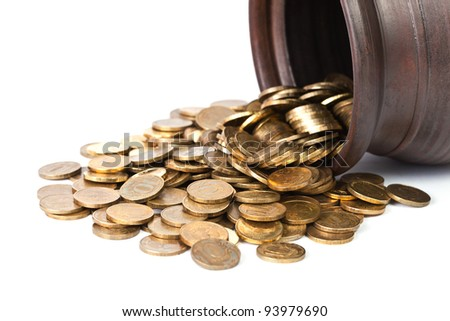 Golden coins falling out from pot close up on white background
