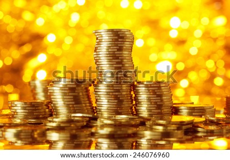 Golden coins stacks on bright light glowing bokeh background, business finance wealth and success concept - stock photo