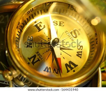 Golden compass on green grass - stock photo