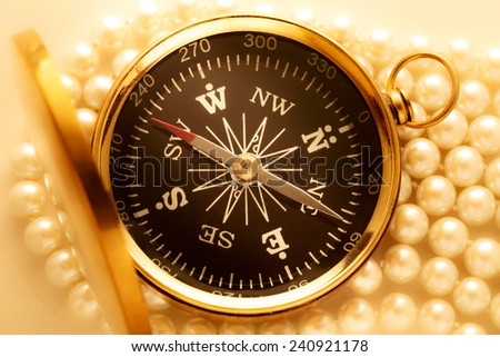 Golden compass on pearl necklace as background - stock photo