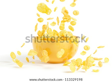 Golden cornflakes falling into the breakfast bowl - stock photo