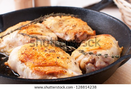 Golden crisp chicken thighs with herbs and spices horizontal - stock photo