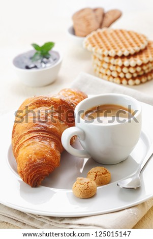 Golden crisp flaky croissant and a cup of rich espresso served with two little macaroons on a plate in a restaurant