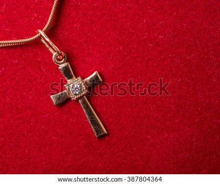 golden cross on a chain on a red textile background - stock photo
