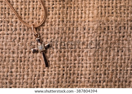 golden cross on a chain on a textile background - stock photo