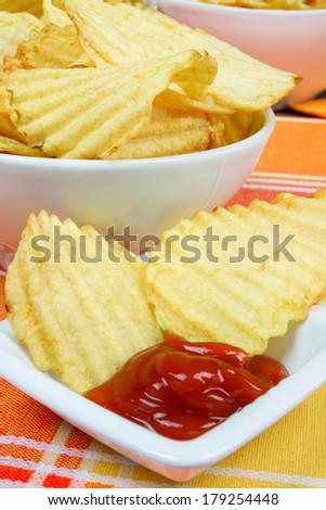 golden crunchy chips grilled on colored background and ketchup sauce
