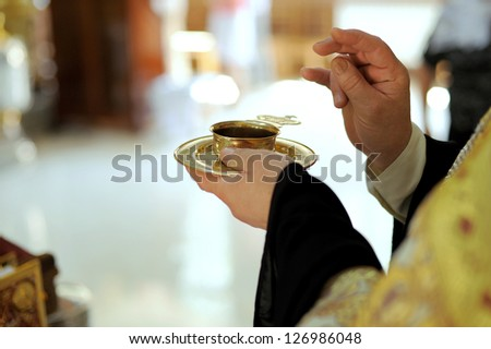 golden cup with red wine on priest's hand - stock photo