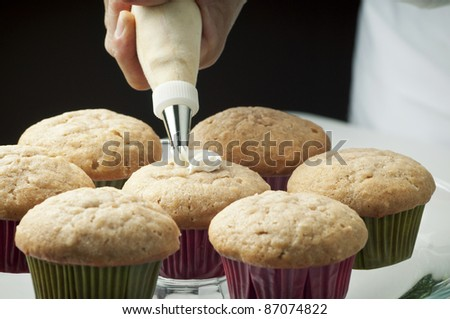 Golden cupcakes with butter cream being piped on by pastry chef/Fresh Baked Cupcakes - stock photo