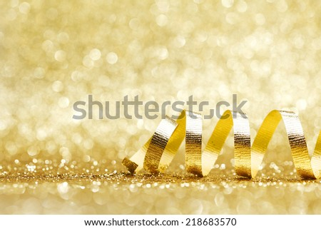 Golden curly ribbon decoration on glitter background close-up - stock photo