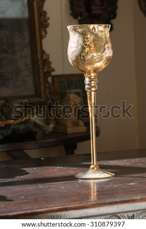 Golden decorated chalice on wooden table and divine light